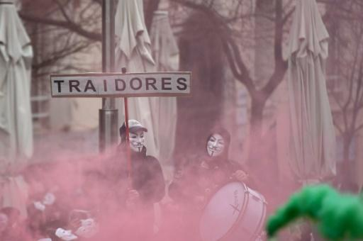 "Police wearing Anonymous masks and carrying a sign reading: ""traitors"" demonstrated outside the parliament in Madrid to demand wage equality with their counterparts in other Spanish regions"
