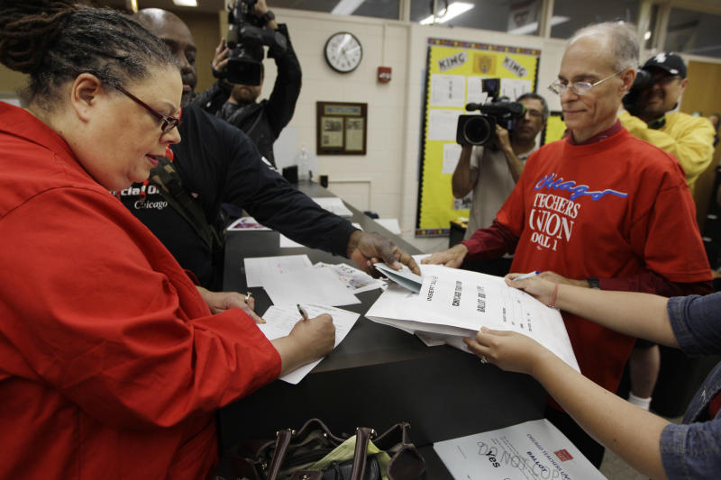 Chicago Teachers Union President Karen Lewis, left, registers for her ballot during a strike authorization vote at a Chicago high school Wednesday, June 6, 2012. Lewis says union members don't want to disrupt the start of the next school year with a strike, but she says they feel voting to authorize one is needed to negotiate a better contract. (AP Photo/M. Spencer Green)