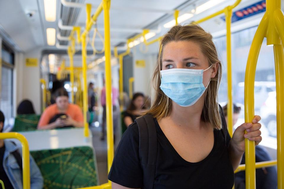 woman wearing disposable mask on public transportation during coronavirus pandemic