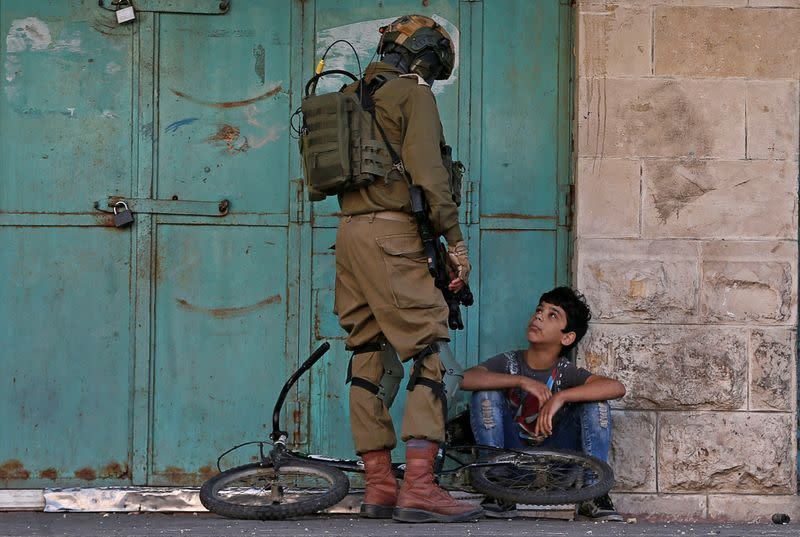 An Israeli soldier detains a Palestinian boy during an anti-Israel protest in Hebron in the Israeli-occupied West Bank