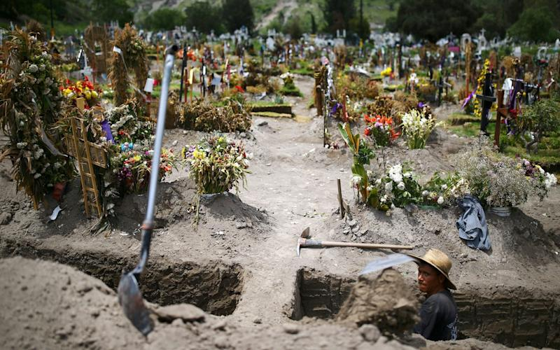 A worker digs new graves at the Xico cemetery on the outskirts of Mexico City - REUTERS/Edgard Garrido