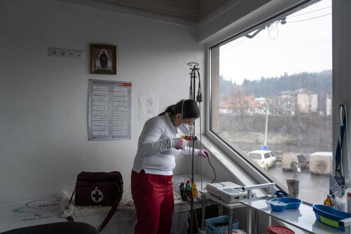 Dr. Viktoria Mahnych, wearing face mask to protect against against coronavirus, prepares an equipment to visit patients with COVID-19 in Verhovyna village, Ivano-Frankivsk region of Western Ukraine, Wednesday, Jan. 6, 2021. Ukraine is struggling to contain the coronavirus pandemic that has inundated its overburdened medical system, as Dr. Viktoria Mahnych goes door to door providing much needed help to patients.(AP Photo/Evgeniy Maloletka)