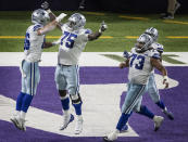 Dallas Cowboys offensive tackle Cameron Erving (75) celebrates tight end Dalton Schultz's (86) winning touchdown catch in the fourth quarter of an NFL football game against the Minnesota Vikings in Minneapolis, Sunday, Nov. 22, 2020. (Jerry Holt/Star Tribune via AP)
