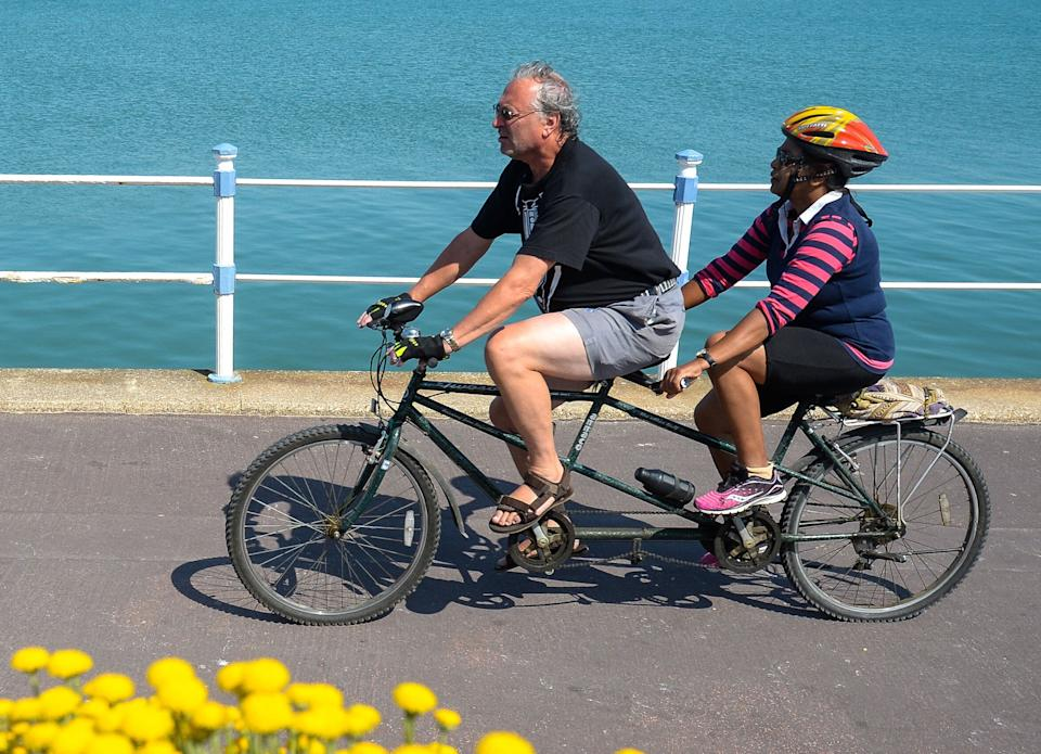 Tandem bike riders cycle along the seafront on June 24 in Weymouth, United Kingdom. Here, the tandem bike frame is clearly longer than the one depicted on the Dunkin' website. (Photo: Finnbarr Webster via Getty Images)