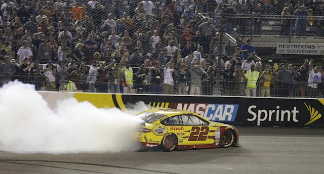 Joey Logano does a burnout following his win in the NASCAR Sprint Cup auto race at Richmond International Raceway in Richmond, Va., Saturday, April 26, 2014. (AP Photo/Steve Helber)