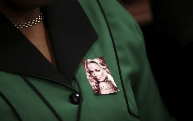 A member of the ANCWL (African National Congress Women's League) wears a picture of late Reeva Steenkamp as she attends Olympic and Paralympic track star Oscar Pistorius murder trial at the North Gauteng High Court in Pretoria, March 5, 2014. Pistorius is on trial for murdering his girlfriend Reeva Steenkamp at his suburban Pretoria home on Valentine's Day last year. He says he mistook her for an intruder. REUTERS/Siphiwe Sibeko (SOUTH AFRICA - Tags: SPORT ATHLETICS CRIME LAW)