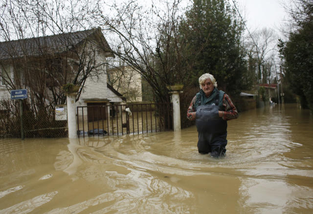 <p>A resident walks in a flooded street of Esbly, east of Paris, where the Grand Morin river floods Thursday, Jan.25, 2018. (Photo: Thibault Camus/AP) </p>