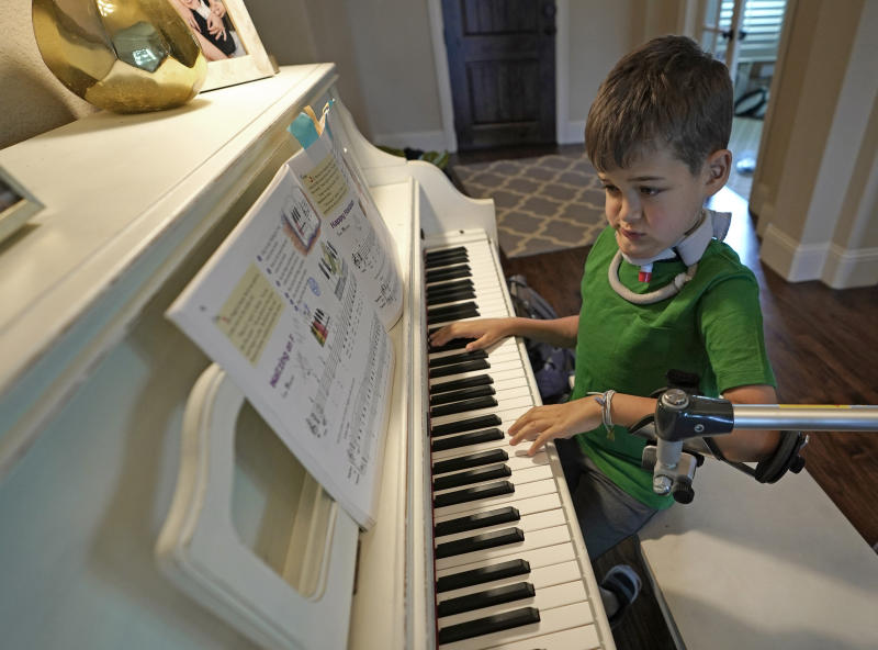 Braden Scott uses a device to support his left arm as he practices on the piano in Tomball, Texas on Friday, March 29, 2019. Braden was diagnosed with the syndrome called acute flaccid myelitis, or AFM, in 2016 and was paralyzed almost completely. The rare but mysterious illness seems to ebb and flow every other year and is beginning to alarm public health officials. (AP Photo/David J. Phillip)