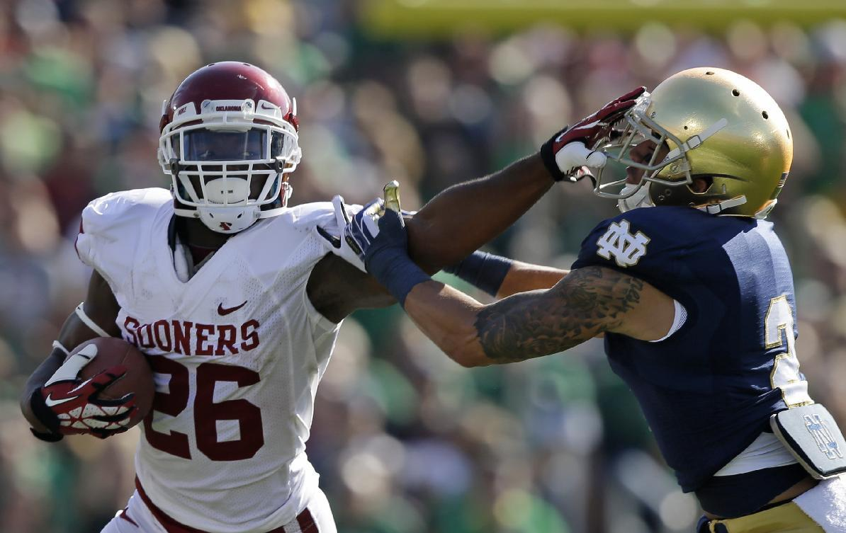 Oklahoma's Damien Williams (26) runs out of the tackle of Notre Dame's Bennett Jackson (2) during the first half of an NCAA college football game on Saturday, Sept. 28, 2013, in South Bend, Ind. (AP Photo/Darron Cummings)