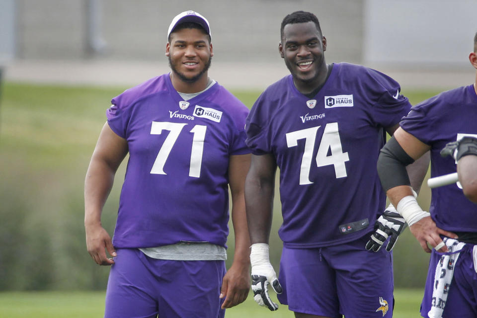 Minnesota Vikings linemen Christian Darrisaw (71) and Oli Udoh (74) smile as they watch drills during NFL football training camp Wednesday, July 28, 2021, in Eagan, Minn. (AP Photo/Bruce Kluckhohn)