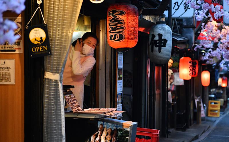 TOKYO, JAPAN - MARCH 19: A woman wearing a face mask looks out from a yakitori restaurant in a traditional dining area on March 19, 2020 in Tokyo, Japan. Japanese authorities announced a small increase in coronavirus cases today with the figure now standing at 924 infections and 33 fatalities. Meanwhile, Hokkaido, the prefecture with the highest number of coronavirus (COVID-19) infections, will end its state of emergency over the epidemic amid signs the spread of the virus is abating there. (Photo by Carl Court/Getty Images)