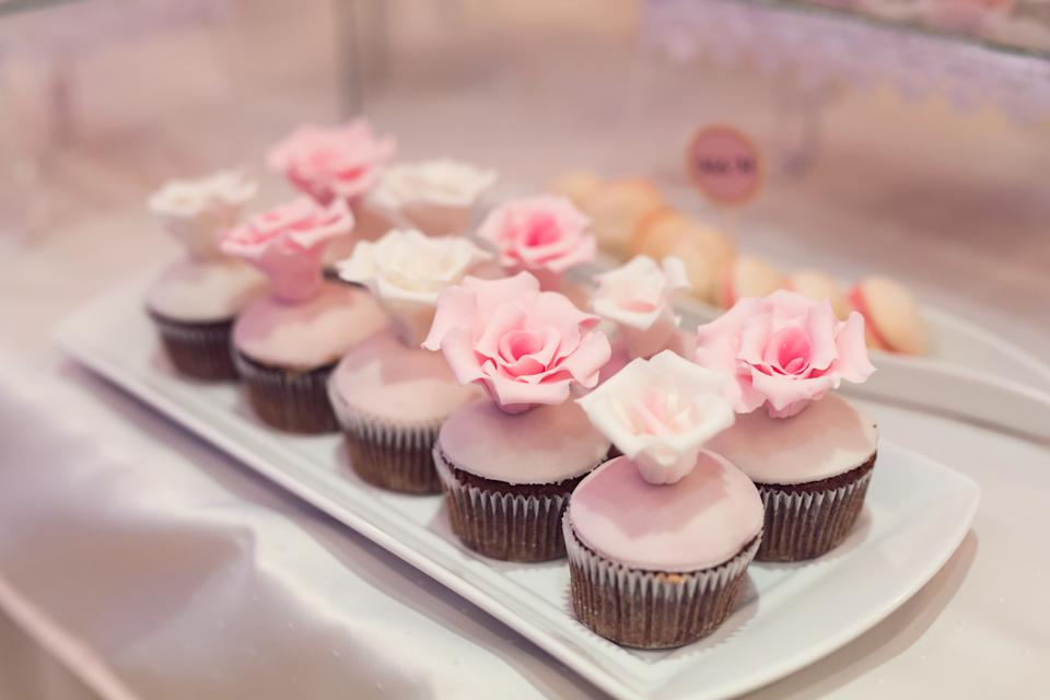 White plate on the table with cupcakes ornate with sweet roses; cookies on the background