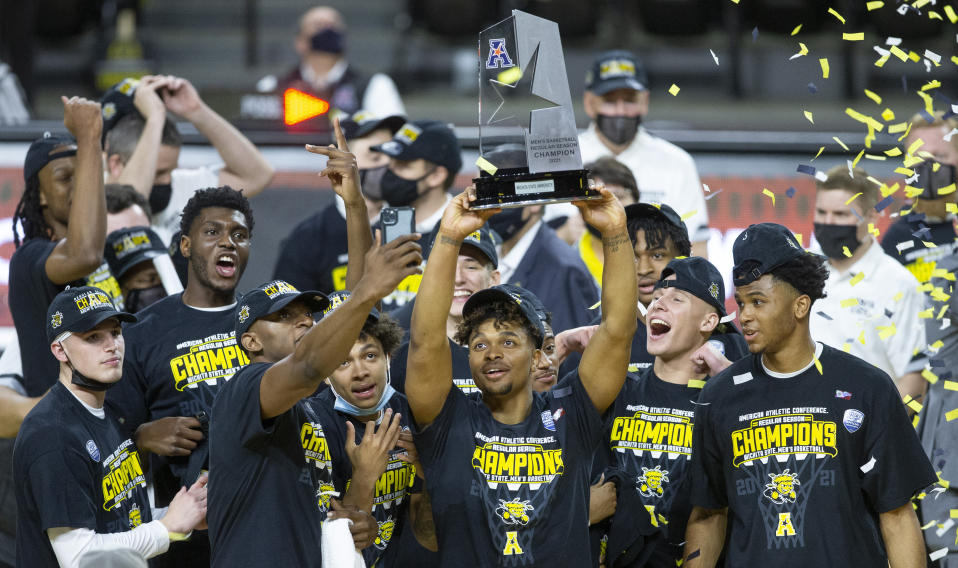 Members of the Wichita State basketball team celebrate after the Shockers clinched the American Athletic Conference men's basketball title on  Saturday, March 6, 2021, in Wichita, Kan. (Travis Heying/The Wichita Eagle via AP)