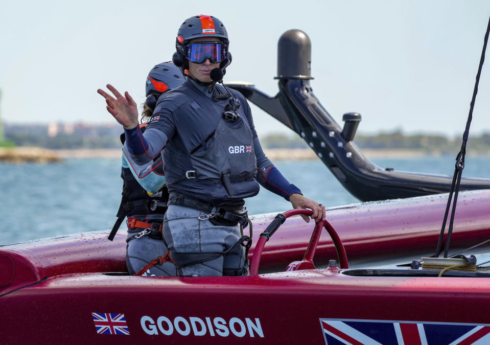 In this photo provided by SailGP, Paul Goodison, interim helmsman of Great Britain SailGP Team, waves from the helm during practice in Taranto, Italy, June 1, 2021. The SailGP global road show touches down in Old Blighty this weekend, giving Goodison the opportunity to sail in front of home crowds for the first time since the 2012 London Olympics. The regatta on Plymouth Sound will also give Australia's Tom Slingsby the chance to bounce back from a last-place performance in the previous regatta, an unthinkable finish for the crack team that claimed the $1 million, winner-take-all prize during the inaugural season of 2019. (Bob Martin/SailGP via AP)