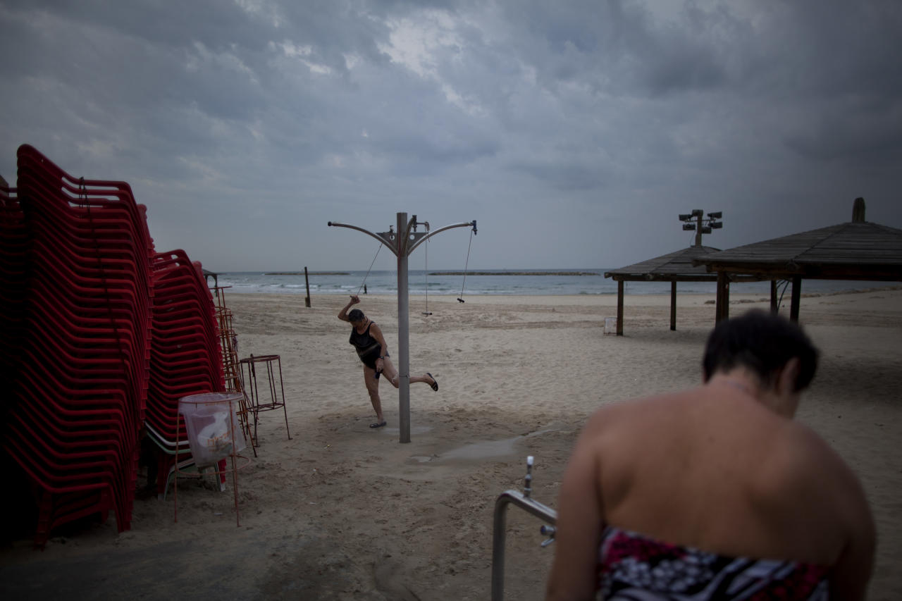 In this Dec. 4, 2012 photo, two immigrants from the Ural region of the former Soviet Union rinse off after bathing in the Mediterranean Sea in the early morning, in Tel Aviv, Israel. Many Soviet immigrants gather at the beach for a traditional winter dip, the closest substitute to the freezing waters of the former Soviet Union. (AP Photo/Oded Balilty)