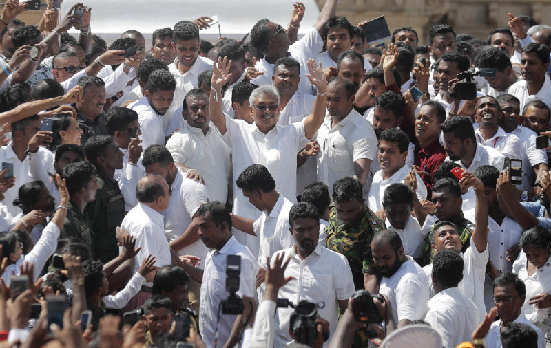 Sri Lanka's newly elected president Gotabaya Rajapaksa, center, greets people as he leaves after the swearing in ceremony held at the 140 B.C Ruwanweli Seya Buddhist temple in ancient kingdom of Anuradhapura in north central Sri Lanka Monday, Nov. 18, 2019. The former defense official credited with ending a long civil war was Monday sworn in as Sri Lanka's seventh president after comfortably winning last Saturday's presidential election. (AP Photo/Eranga Jayawardena)