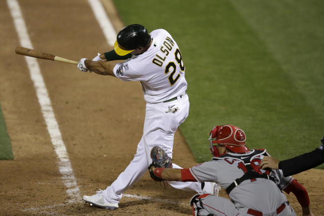 Oakland Athletics' Matt Olson, left, hits a grand slam home run in front of Los Angeles Angels catcher Jason Castro in the tenth inning of a baseball game in Oakland, Calif., Friday, July 24, 2020. The Athletics won 7-3 in 10 innings. (AP Photo/Jeff Chiu)