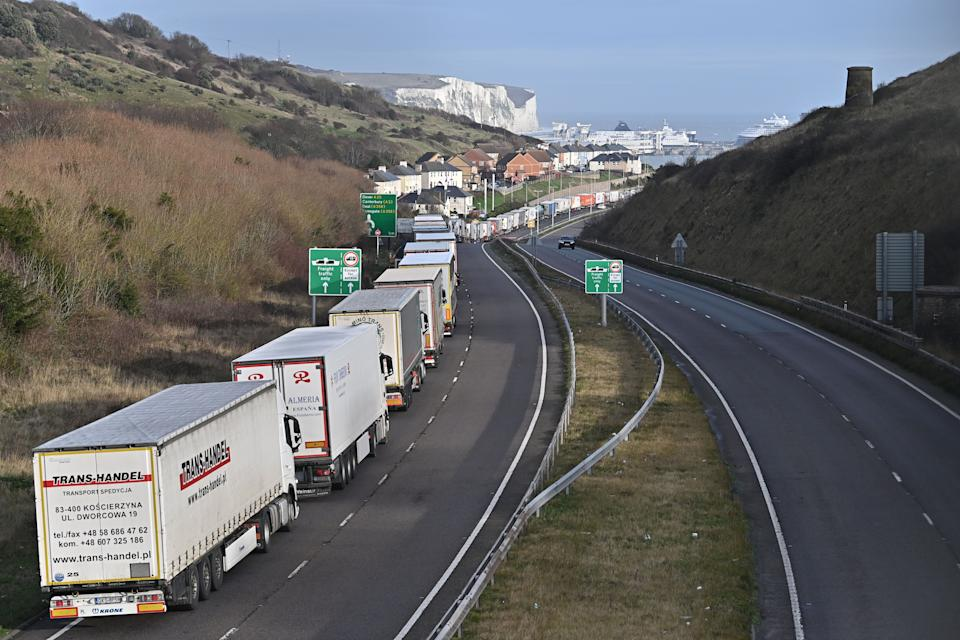The Dover Traffic Access Protocol (TAP) scheme on the A20 is seen in action as freight lorries queue on the main route into the port of Dover on the south coast of England on December 18, 2020 with the White Cliffs and a ferry in the background. - Questions were asked in the House of Lords on December 17 on the government's state of preparedness for Brexit. UK importers are suffering from delays at Felixstowe and Southampton and there are fears of major delays at Dover from the new year. (Photo by Ben STANSALL / AFP) / The erroneous mention[s] appearing in the metadata of this photo by Ben STANSALL has been modified in AFP systems in the following manner: Picture taken on [December 18, 2020] instead of [December 17, 2020]. Please immediately remove the erroneous mention[s] from all your online services and delete it (them) from your servers. If you have been authorized by AFP to distribute it (them) to third parties, please ensure that the same actions are carried out by them. Failure to promptly comply with these instructions will entail liability on your part for any continued or post notification usage. Therefore we thank you very much for all your attention and prompt action. We are sorry for the inconvenience this notification may cause and remain at your disposal for any further information you may require. (Photo by BEN STANSALL/AFP via Getty Images)