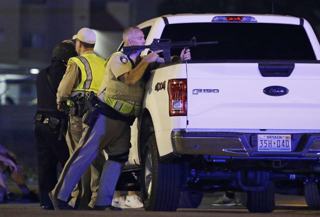 <p>A police officer takes cover behind a truck at the scene of a shooting near the Mandalay Bay resort and casino on the Las Vegas Strip, Oct. 1, 2017, in Las Vegas. Multiple victims were being transported to hospitals after a shooting late Sunday at a music festival on the Las Vegas Strip. (AP Photo/John Locher) </p>