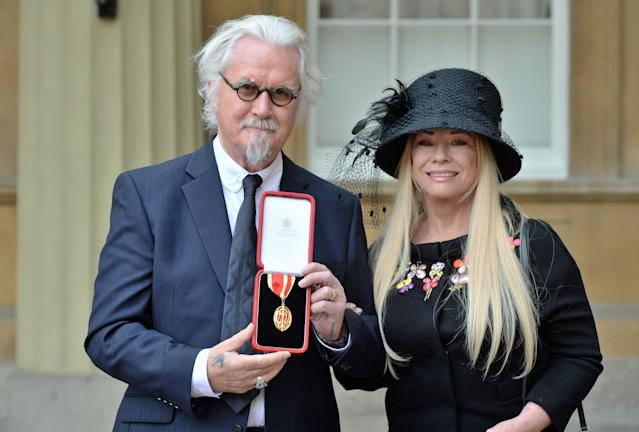 Sir Billy Connolly poses with his wife Pamela Stephenson, after being knighted by the Duke of Cambridge in London, United Kingdom. (Photo by John Stillwell - WPA Pool / Getty Images)