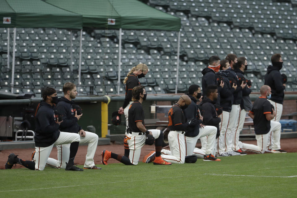 San Francisco Giants players and coaches kneel with others during the national anthem before an exhibition baseball game against the Oakland Athletics in San Francisco, Tuesday, July 21, 2020. (AP Photo/Jeff Chiu)
