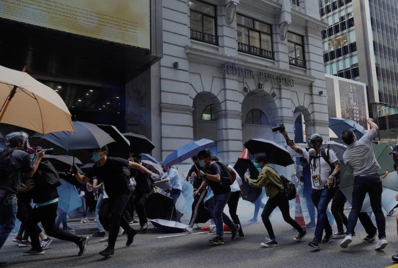 Protesters with umbrellas run after tear gas are fired in Hong Kong on Monday, Nov. 11, 2019. A protester was shot by police Monday in a dramatic scene caught on video as demonstrators blocked train lines and roads during the morning commute. (AP Photo/Vincent Yu)