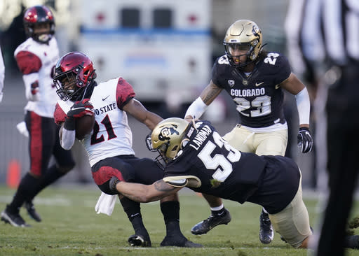 San Diego State running back Chance Bell, left, is pulled down by Colorado linebacker Nate Landman (53) after a short gain as Colorado safety Isaiah Lewis follows the play in the first half of an NCAA college football game Saturday, Nov. 28, 2020, in Boulder, Colo. (AP Photo/David Zalubowski)