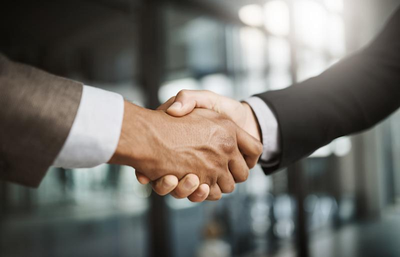 Cropped shot of two unrecognizable businessmen shaking hands in a modern office