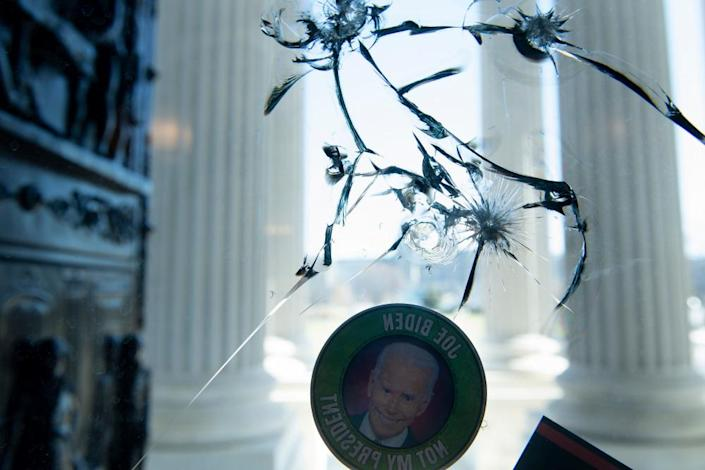 An anti-Biden sticker is seen on a cracked window a day after a pro-Trump mob broke into the US Capitol.