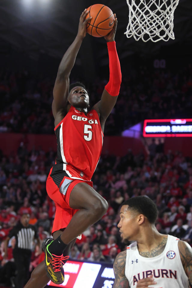 Georgia guard Anthony Edwards (5) goes up to score next to Auburn guard J'Von McCormick during the second half of an NCAA college basketball game Wednesday, Feb. 19, 2020, in Athens, Ga. Georgia won 65-55. (AP Photo/John Amis)