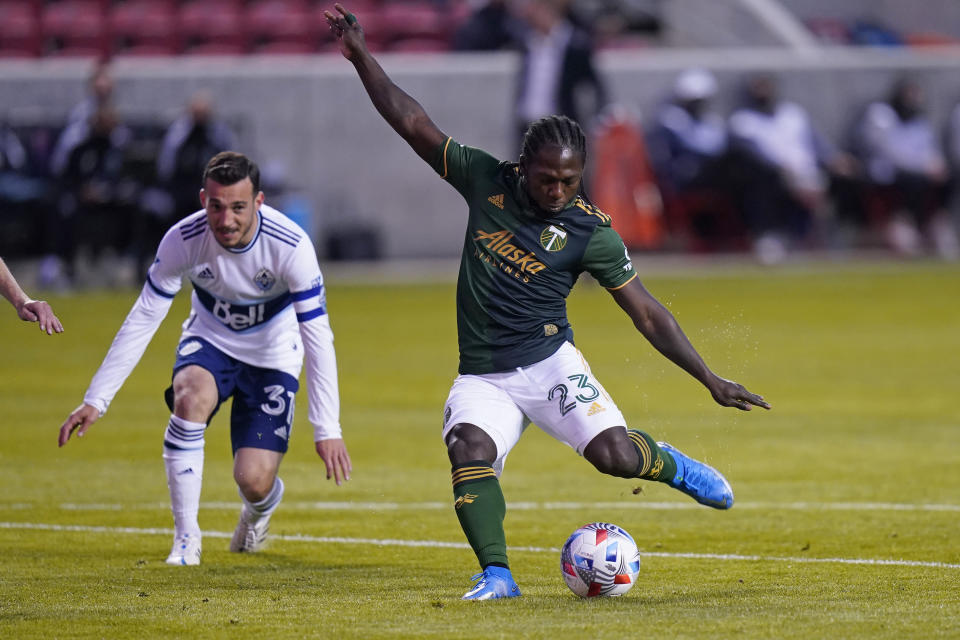 Portland Timbers forward Yimmi Chara (23) shoots as Vancouver Whitecaps midfielder Russell Teibert (31) looks on in the first half during an MLS soccer game Sunday, April 18, 2021, in Sandy, Utah. (AP Photo/Rick Bowmer)