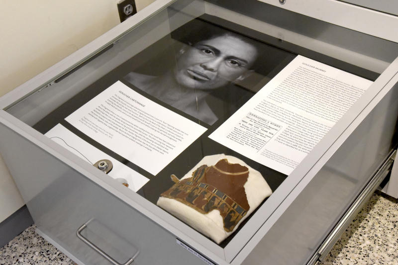 "In a Sept. 26, 2018 photo, a pull-out drawers offer more information about the facial depiction process at the new Johns Hopkins Archaeological Museum exhibit, ""Who Am I? Remembering the Dead Through Facial Reconstruction,"" in Baltimore. Pictured here is the facial depiction of the Goucher mummy, and her ""boot."" FaceLab, Liverpool John Moores University, worked with Hopkins to create facial depictions of the Goucher mummy, ca. 4th c. BCE, and the Cohen mummy, ca. 664 - 525 BCE. (Amy Davis/The Baltimore Sun via AP)"