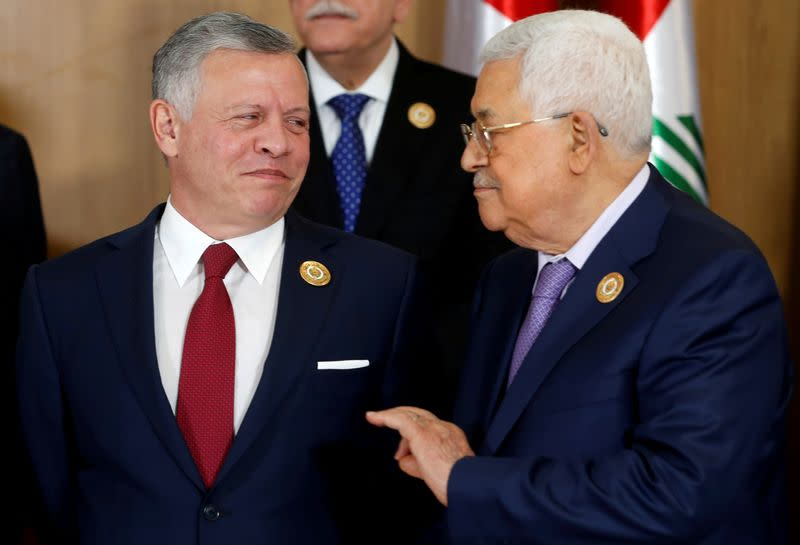 FILE PHOTO: Jordan's King Abdullah II speaks with Palestinian President Mahmoud Abbas during the group photo with Arab leaders, ahead of the 30th Arab Summit in Tunis