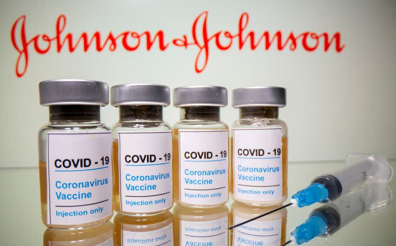 FILE PHOTO: Vials and medical syringe are seen in front of J&J logo in this illustration