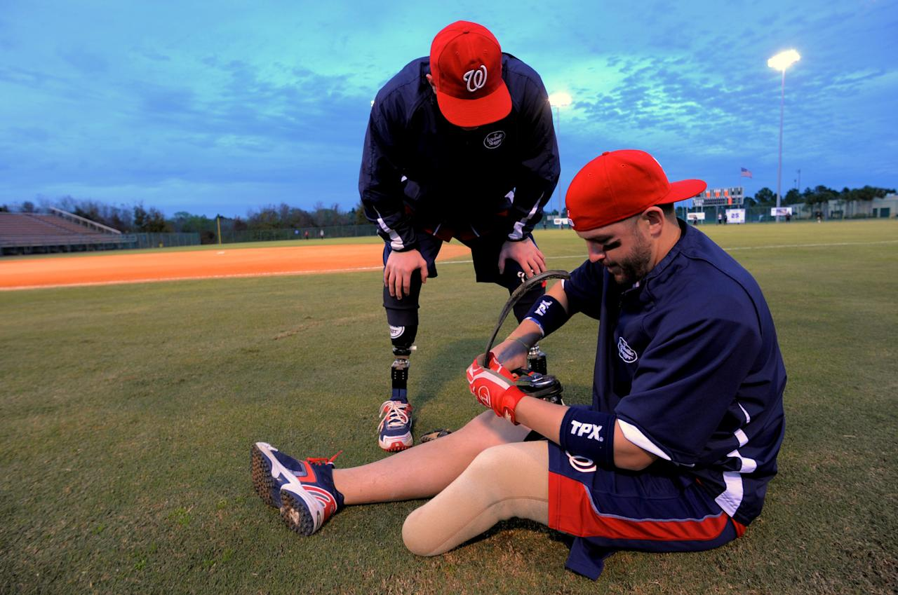 In this Friday, Jan. 13, 2012, photo, Wounded Warrior Amputee Softball Team member Joshua Wege, left, assists teammate Daniel Lasko as he uses a wrench to repair his prosthetic leg before an exhibition game against the Fellowship of Christian Athletes, which features former Olympic softball team members Jennie Finch and Dot Richardson, in Plant City, Fla. (AP Photo/Brian Blanco)