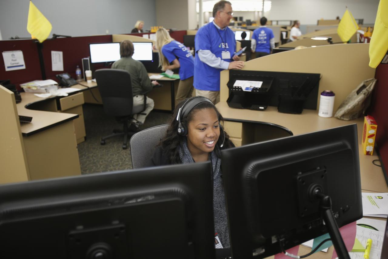 """Shaldonia Barney (front), a service agent at Covered California's Concord call center, takes a call during the opening day of enrollment of the Patient Protection and Affordable Care Act in Concord, California October 1, 2013. Better known as """"Obamacare,"""" the Affordable Care Act requires health insurance companies to provide a basic package of benefits and prohibits them from excluding people due to prior illnesses. The Act will provide billions of dollars in government subsidies, in the form of tax credits, to help individuals buy insurance on the basis of annual income from the health insurance marketplace such as Covered California, a state-implemented exchange. REUTERS/Stephen Lam (UNITED STATES - Tags: HEALTH POLITICS BUSINESS)"""