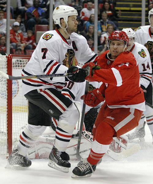 Chicago Blackhawks' Brent Seabrook (7) tries to clear Detroit Red Wings' Luke Glendening (41) from in front of the net during the second period of a preseason NHL hockey game Sunday, Sept. 22, 2013 in Detroit. (AP Photo/Duane Burleson)