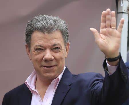 President Juan Manuel Santos greets the media before casting his vote Bogota