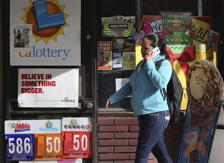 A woman walks past a Mega Millions lottery sign with the estimated jackpot of $586 million posted in Los Angeles, California December 16, 2013. REUTERS/Jonathan Alcorn