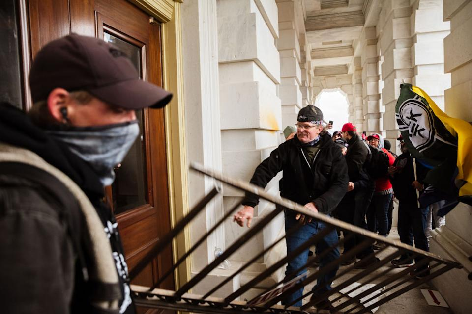 A member of a pro-Trump mob bashes an entrance of the Capitol Building in an attempt to gain access in Washington, DC.