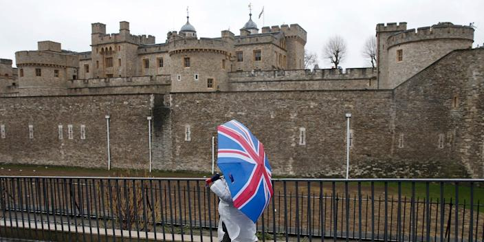 A person carrying a Union Jack umbrella walks by the Tower of London in January 2017.