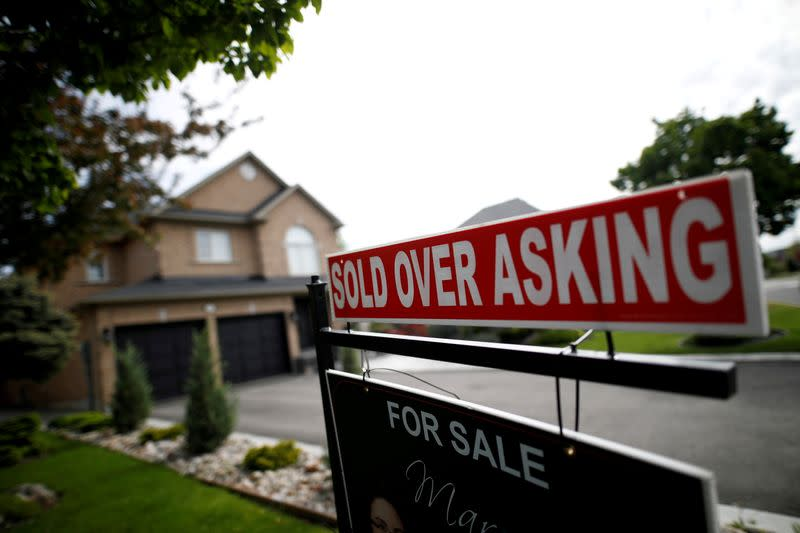 """FILE PHOTO: A real estate sign that reads """"For Sale"""" and """"Sold Above Asking"""" stands in front of housing in Toronto"""