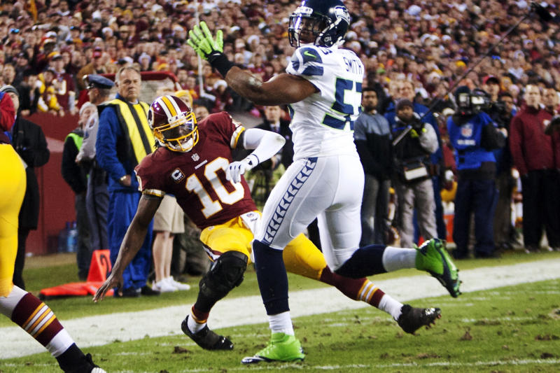 In this Jan. 6, 2013, photo, Washington Redskins quarterback Robert Griffin III (10) hurts his right knee as he falls awkwardly while throwing an incomplete pass under pressure from Seattle Seahawks linebacker Malcolm Smith (53) during the first quarter of their NFL wild card playoff football game in Landover, Md. An injury that sidelines Griffin well into next season is a very real possibility _ or at least it seemed that way Monday, Jan. 7, after head coach Mike Shanahan described the results of tests on the rookie's right knee following a series of plays in their Sunday game that did additional damage to a knee that was just three games removed from suffering a sprained lateral collateral ligament. (AP Photo/The Virginian-Pilot, L. Todd Spencer) MAGS OUT