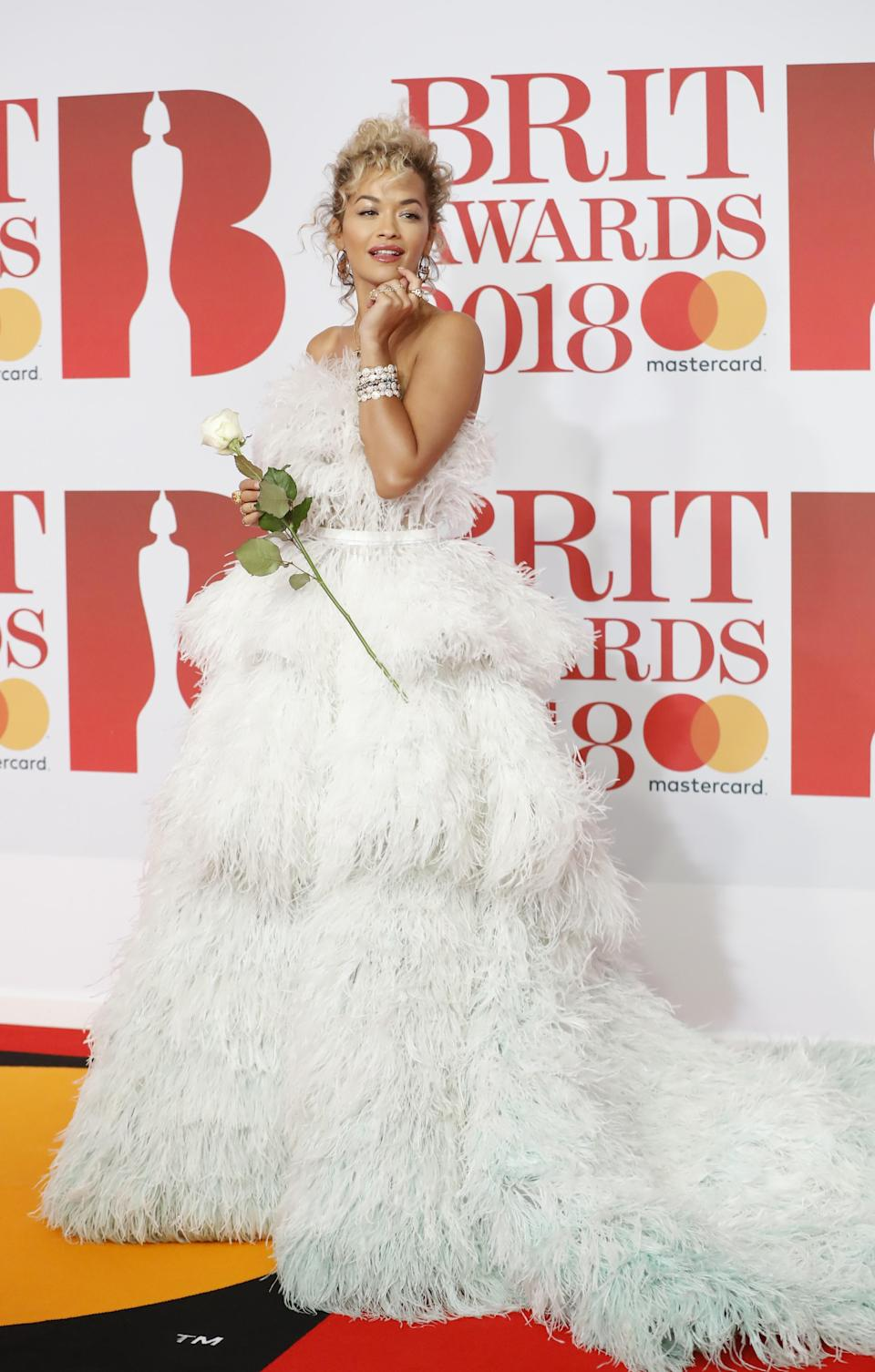 Rita Ora holding a white rose at the Brit Awards to show support for the Time's Up movement [Photo: Getty]