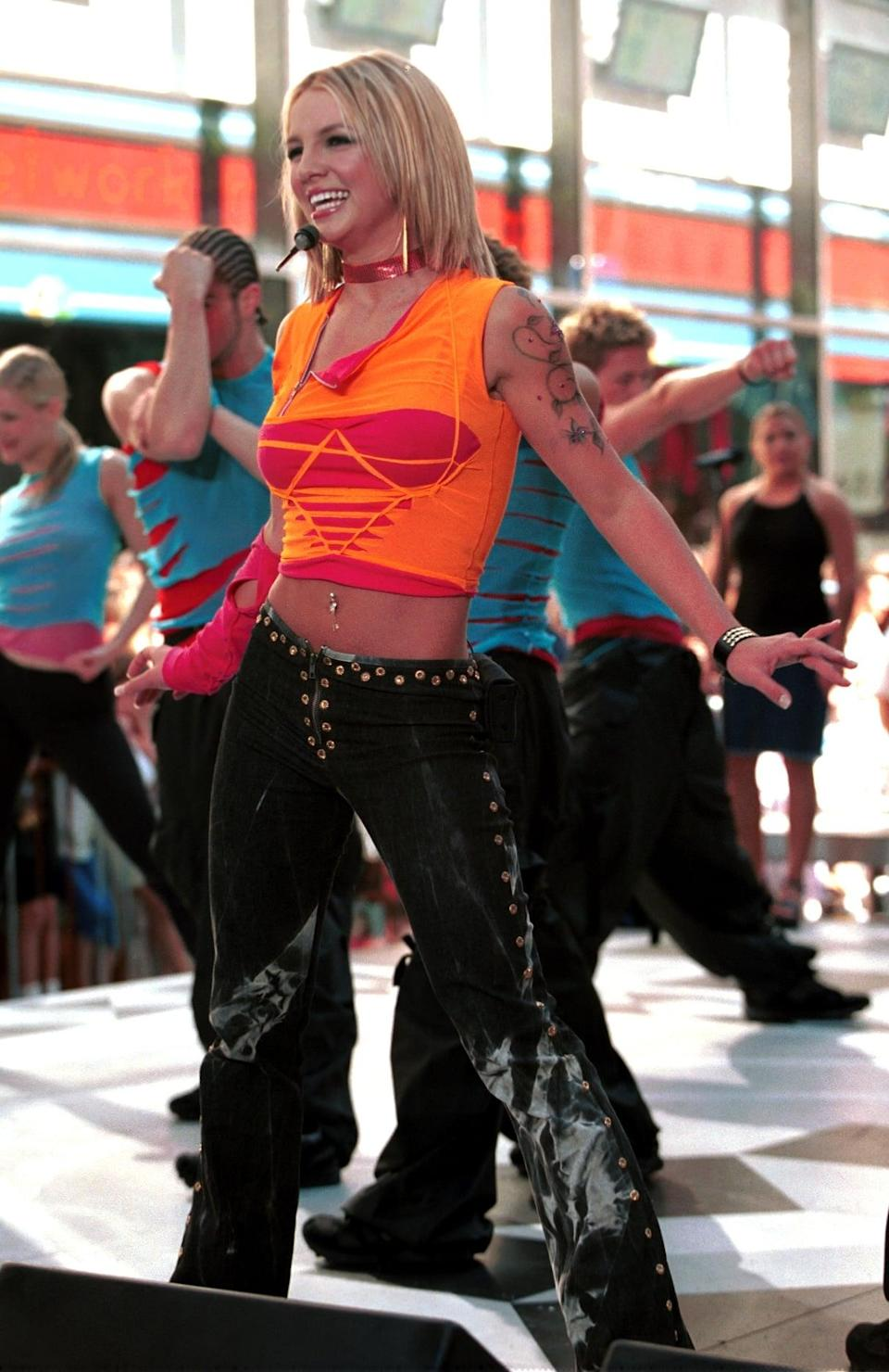<p>Performing in a cutout crop top and studded pants.</p>