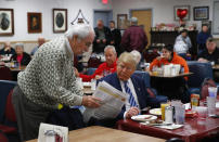 FILE - Republican presidential candidate Donald Trump looks at a newspaper with a diner at Tommy's Country Ham House, Tuesday, Feb. 16, 2016, in Greenville, S.C. For decades, Tommy's Country Ham House has hosted presidential candidates testing their mettle among voters in South Carolina. But the Greenville landmark has announced that it is turning off the fryer and shutting its doors. Owner Tommy Stevenson announced Sunday, Jan. 31, 2021 that Tommy's would close this spring. (AP Photo/Paul Sancya, file)