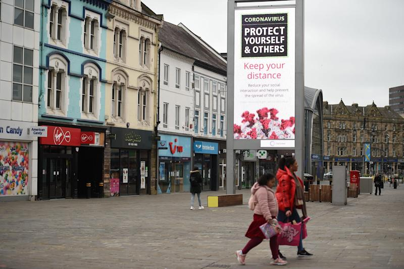 People walk in a high street with signs advising people to observe social distancing in Newcastle upon Tyne: AFP via Getty Images