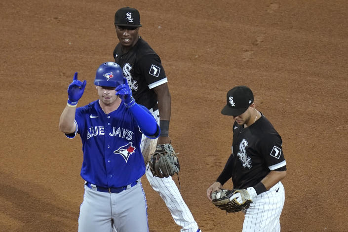 Toronto Blue Jays' Riley Adams celebrates his first hit in the majors, a double off Chicago White Sox starting pitcher Carlos Rodon, as White Sox's Tim Anderson, top, and Nick Madrigal stand nearby during the fifth inning of a baseball game Tuesday, June 8, 2021, in Chicago. (AP Photo/Charles Rex Arbogast)