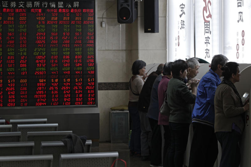Chinese investors check stock prices at a brokerage house in Beijing, Monday, April 8, 2019. Shares are mixed in Asia, after trade talks between China and the U.S. wrapped up with officials on both sides claiming progress. (AP Photo/Andy Wong)
