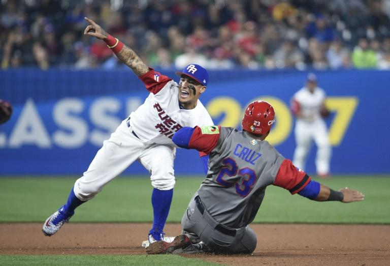 Javier Baez (L) of Puerto Rico tags out Nelson Cruz of Dominican Republic as he tries to steal second base during the eighth inning of their World Baseball Classic Pool F game, at PETCO Park in San Diego, California, on March 14, 2017